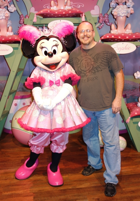 I need a fun idea for a mid-forties married man with children to pose with Minnie Mouse in this location.  I can't do the dancer pose!